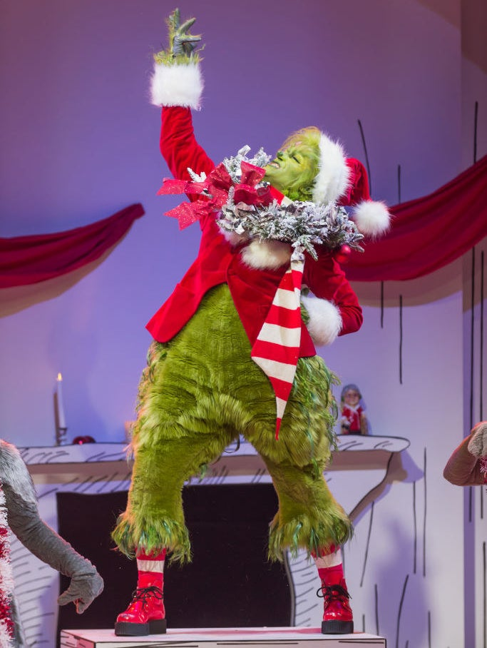 Matthew Morrison in his Grinch costume posing on a table with one arm up and the other on his hip.