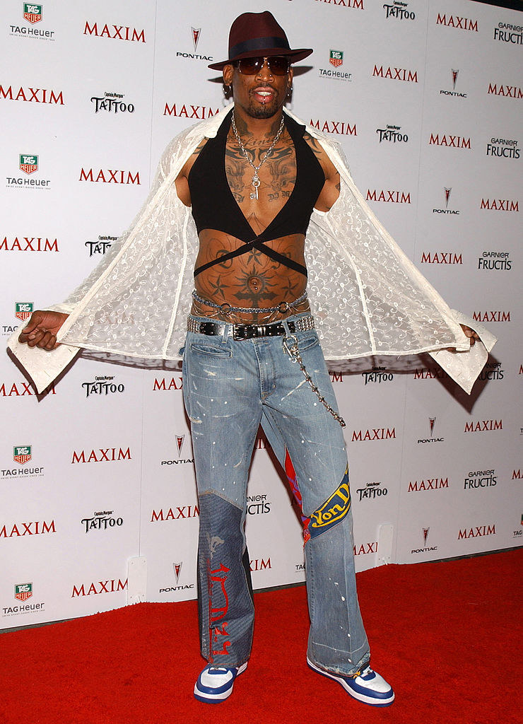 Dennis in a black twisty bralette crop top with a lacy open button up above it and jeans