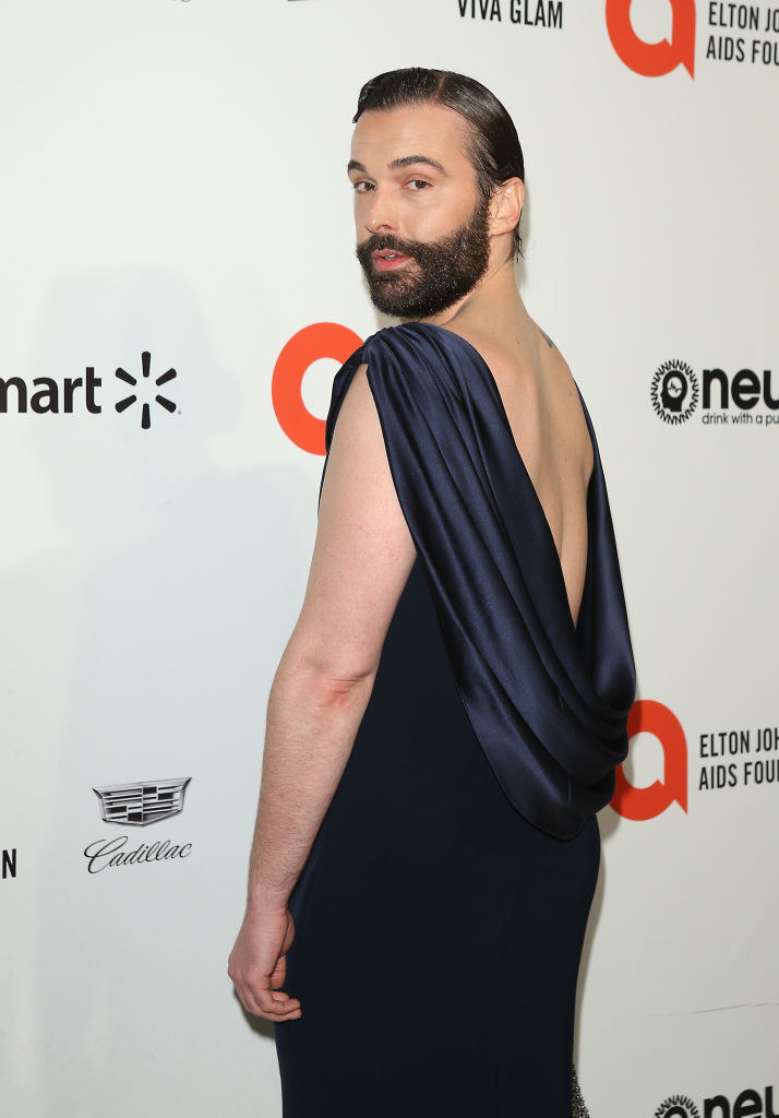 Jonathan in a long sleeve dress with an open back and a large satin cowl