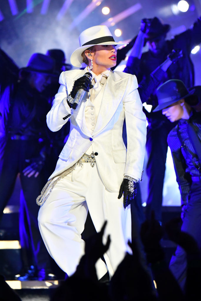 white 3-piece suit with a tie and vest underneath with a rhinestone belt and cuffs and loose pants