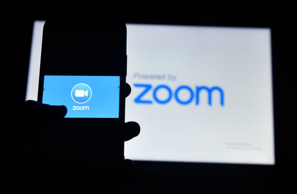 Photo of a hand loading the Zoom app logo onto their smart phone